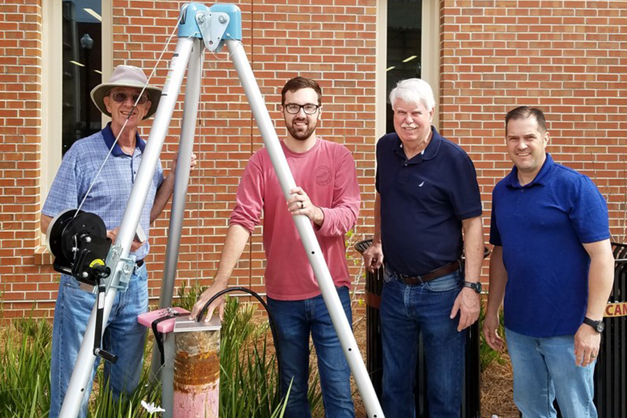The seismometer is installed outside of the new EOAS building. (From left) Bob Hutt, geology graduate student James Eke, former EOAS chair James Tull and assistant research specialist Gary White.